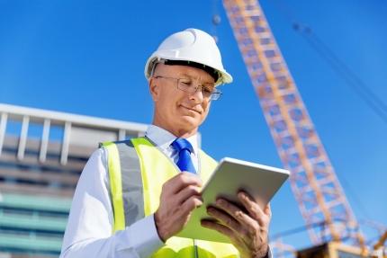 Man met helm en tablet op bouwplaats (klein)